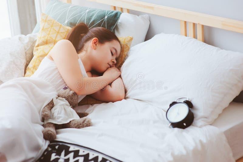 哄骗睡觉在清早的女孩在与闹钟的床上 库存图片