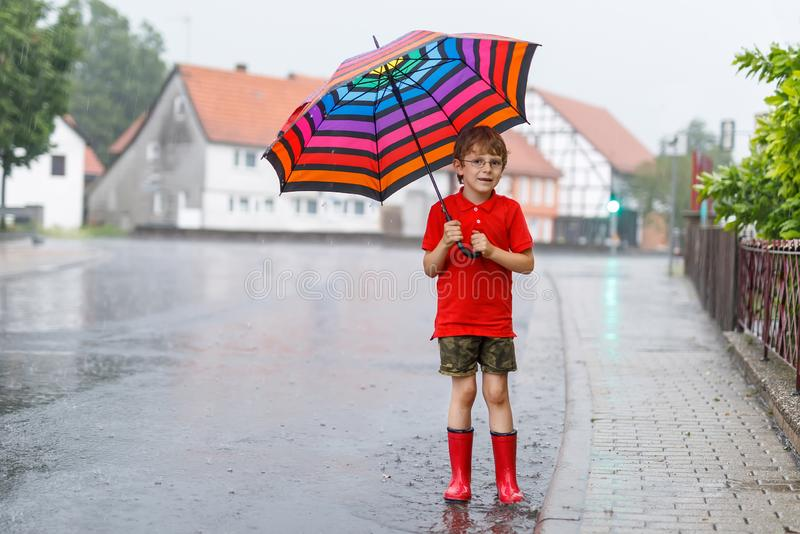 哄骗穿红色雨靴和走与在城市街道上的五颜六色的伞的男孩 戴眼镜的孩子在夏日 免版税库存照片