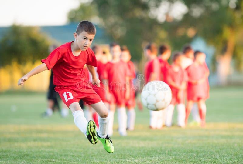 哄骗足球橄榄球-儿童球员在足球场配比 免版税图库摄影