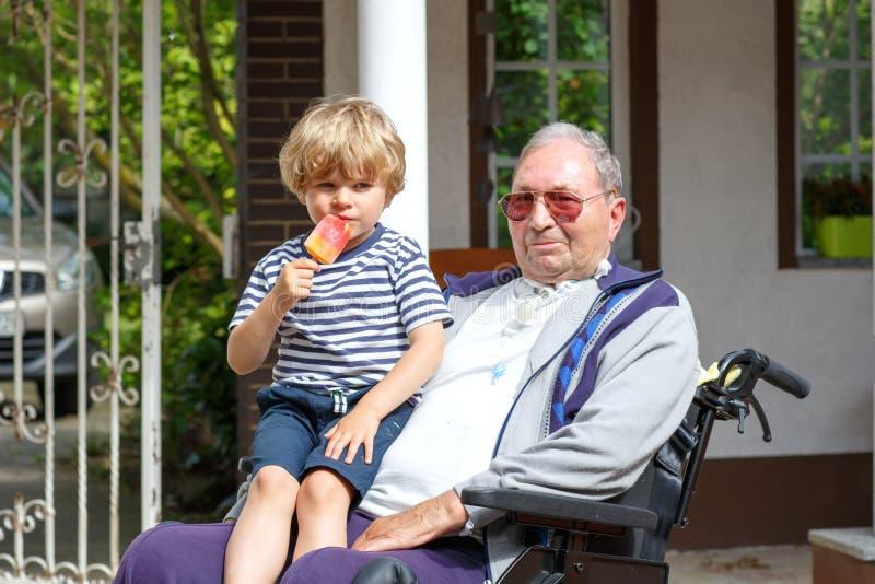 哄骗轮椅的吃冰淇凌的男孩和祖父 库存照片