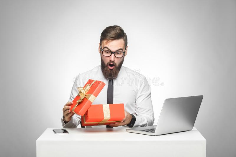哇!白色衬衫的惊奇的年轻经理和半正式礼服在办公室和箱中取出的礼物坐与震惊面孔,大眼睛 免版税库存图片