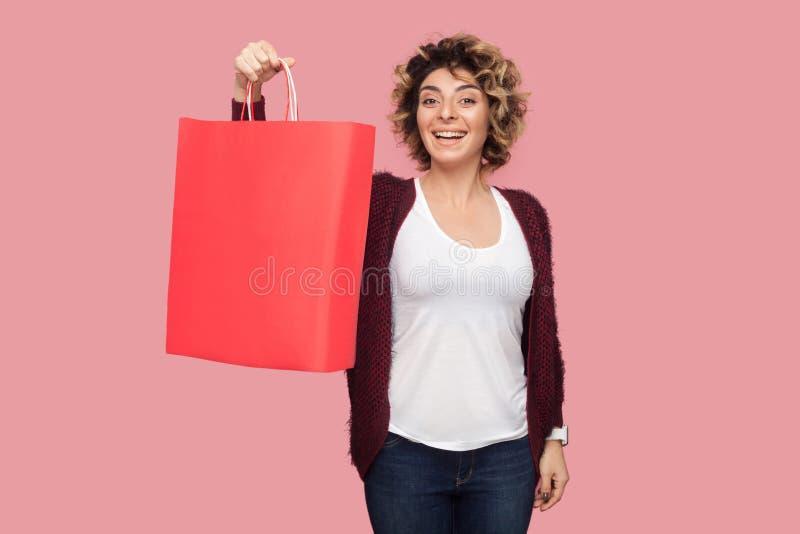 哇!蓝色衬衣的满意的现代年轻女人有curlty发型身分和显示购物带来和暴牙的微笑的,看 图库摄影