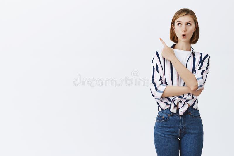 哇,吸引 好奇健谈年轻女性工友画象镶边女衬衫的,折叠的嘴唇,注视和 免版税库存照片