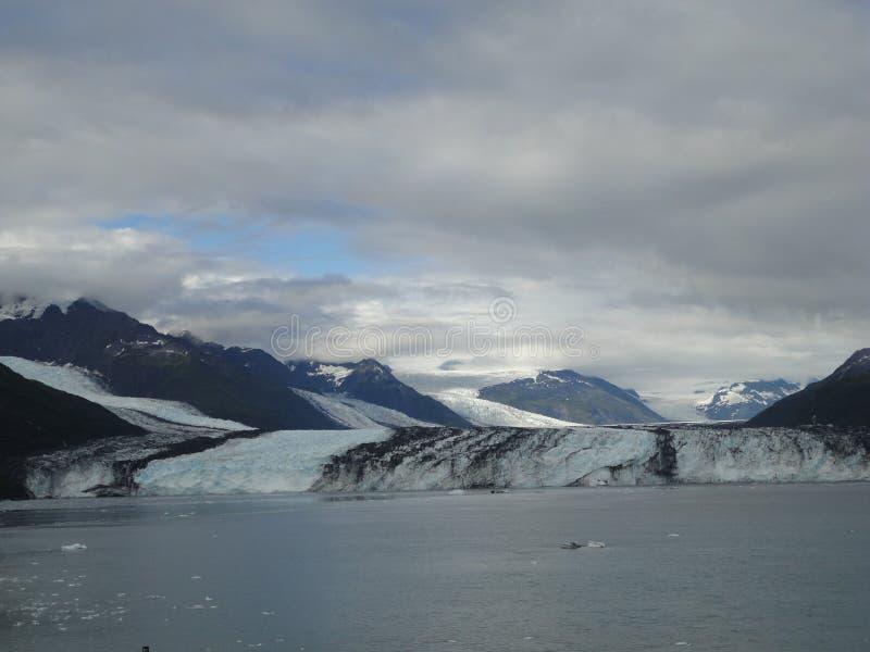 哈佛冰川在学院海湾阿拉斯加末端 雕刻它的道路的宽冰川对海 山峰水和云彩 免版税库存图片