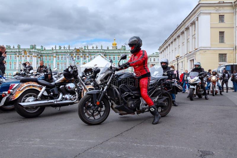 哈利戴维森摩托车节日-盔甲的妇女骑自行车的人和一红色皮夹克和长裤在平方的宫殿乘坐摩托车 库存照片