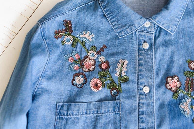 哈尔科夫,乌克兰- 2019年4月27日:花绣与在一件蓝色牛仔布衬衣的衣服饰物之小金属片 衣裳概念 衬衣细节  图库摄影
