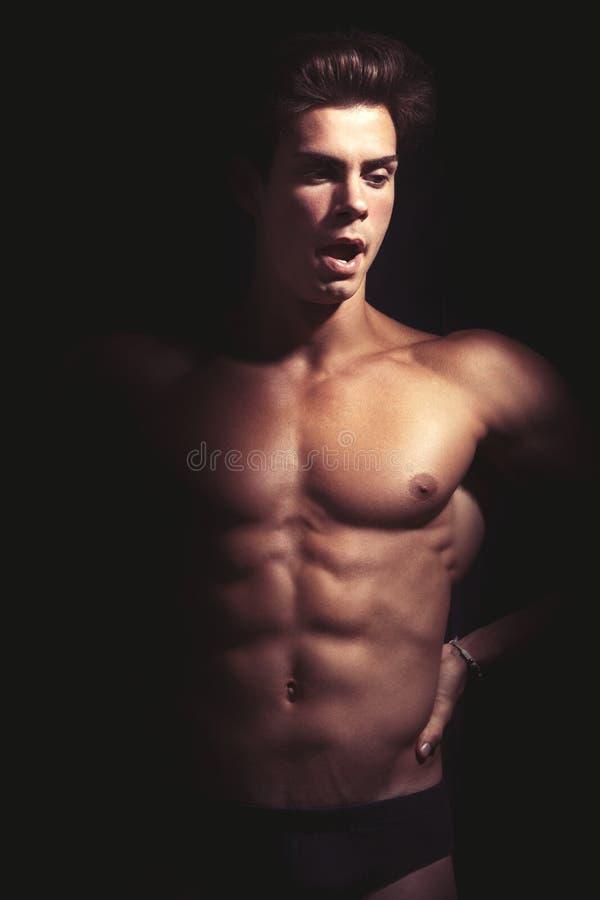 哈欠 打呵欠英俊的肌肉的人 赤裸在黑色 库存图片
