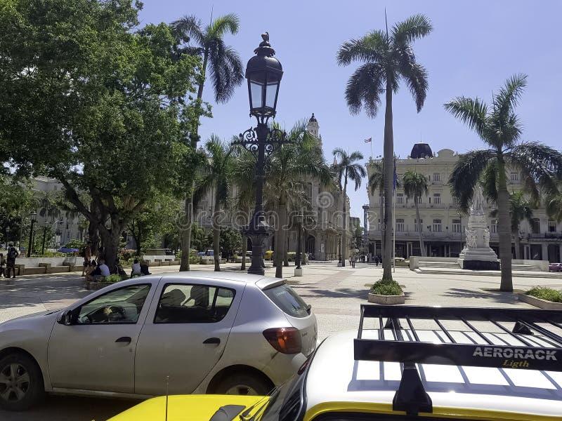 哈瓦那大广场有汽车、游人、棕榈树和旅馆的在背景中 免版税库存图片