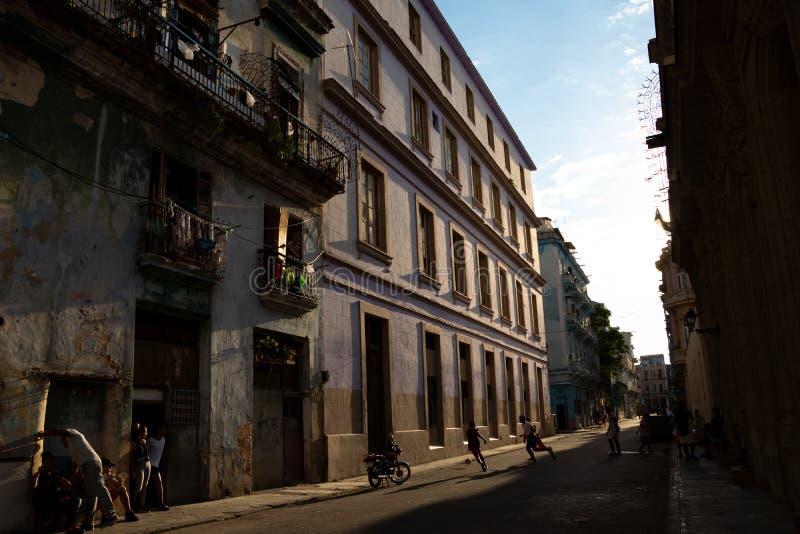 03/26/2019哈瓦那,古巴,在平衡的光的街道场面与聊天他们的房子外的男孩踢橄榄球的和成人 免版税库存图片