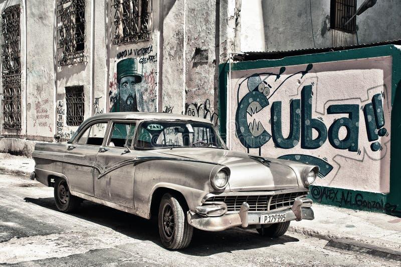 哈瓦那,古巴2018年3月15日:在哈瓦那街道的老汽车有墙壁的绘与古巴宣传 库存图片