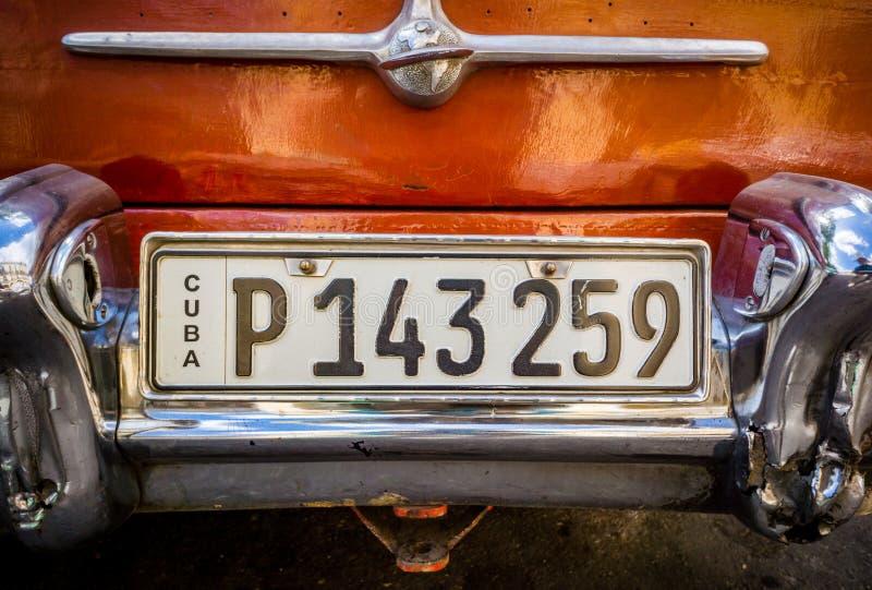 哈瓦那,古巴- 2015 10月29日,古巴人在使用作为在哈瓦那旧城, Havan街道上的出租汽车的薛佛列汽车的牌照 库存照片