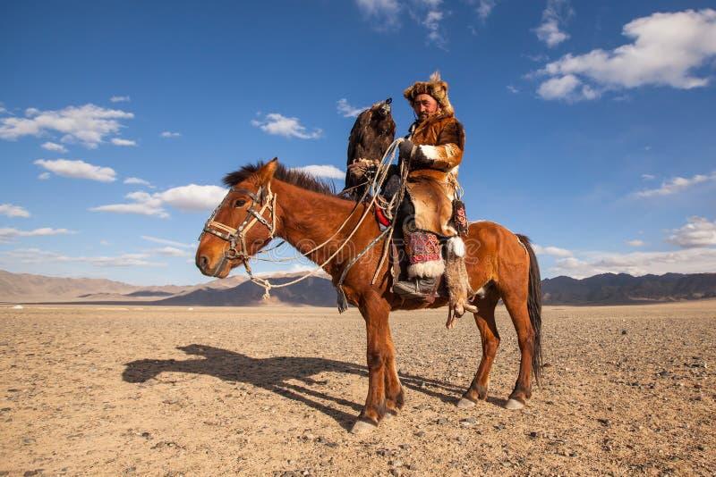哈萨克人在传统衣物的老鹰猎人,在马背上,当寻找对拿着在他的胳膊时的野兔一只鹫 图库摄影