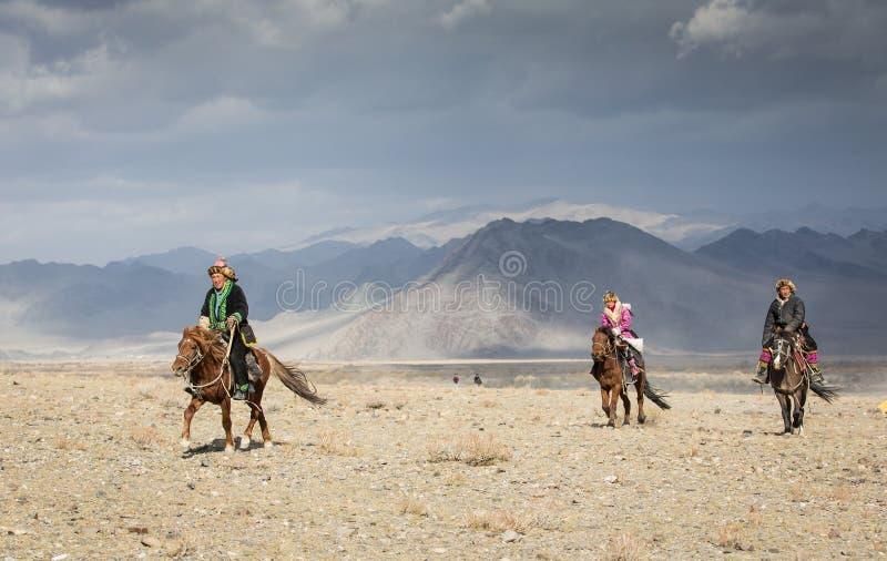 哈萨克人在他们的马的老鹰猎人 免版税库存图片