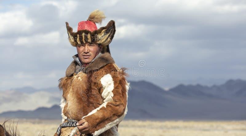 哈萨克人旅行在altai山风景的hgis hotse的老鹰猎人  免版税图库摄影