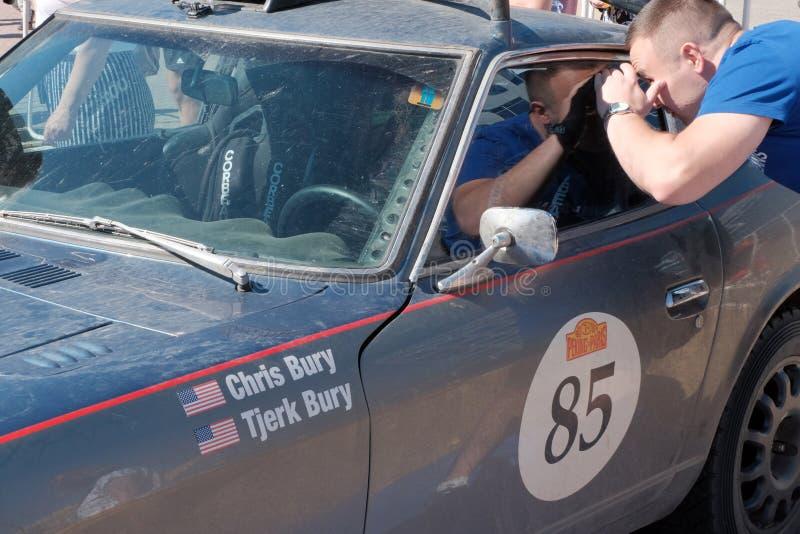 哈萨克斯坦,库斯塔奈,19-06-19,召集北京到巴黎 一个人看一辆老种族汽车的窗口 美国国旗和名字 免版税库存照片