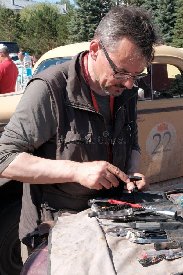 哈萨克斯坦,库斯塔奈,19-06-19,召集北京到巴黎 一辆减速火箭的汽车的司机拿着修理工具 玻璃的技工与 免版税库存照片