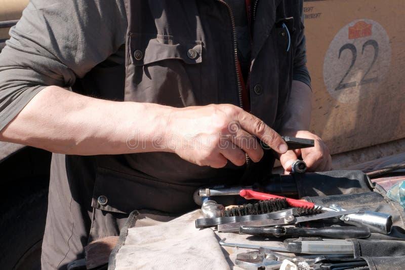 哈萨克斯坦,库斯塔奈,19-06-19,召集北京到巴黎 男性手和汽车修理工具特写镜头  拿着钳子的技工和 免版税库存照片