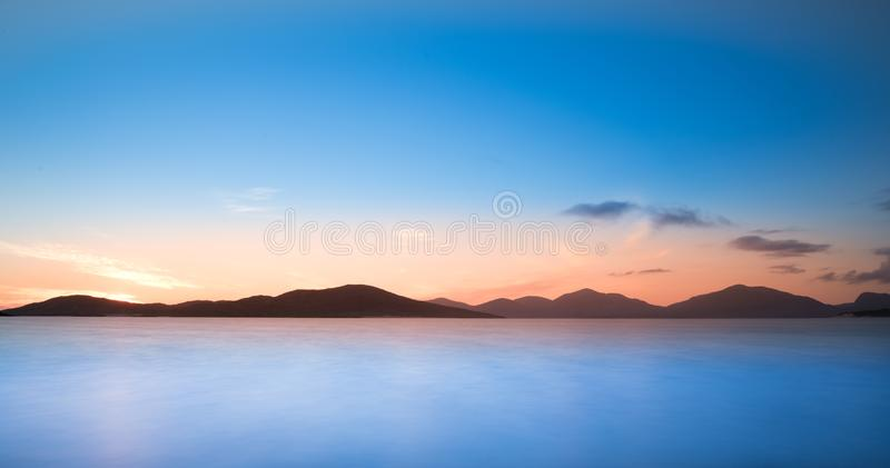 哈里斯风景小岛-在山、美丽的不尽的沙滩和绿松石海洋的日落天空 库存图片