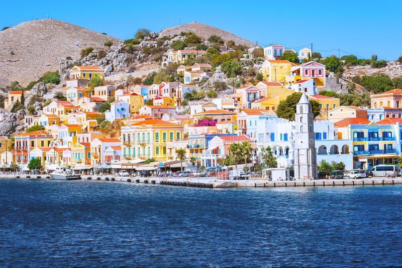 响铃塔和五颜六色的新古典主义的房子在锡米岛锡米岛海岛,希腊港口镇  免版税库存图片