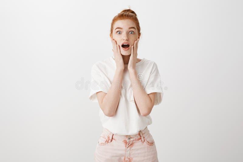 哎呀,了不起的新闻 悦目被打动的和兴奋的年轻白种人女性画象有红色头发的,滴下 图库摄影
