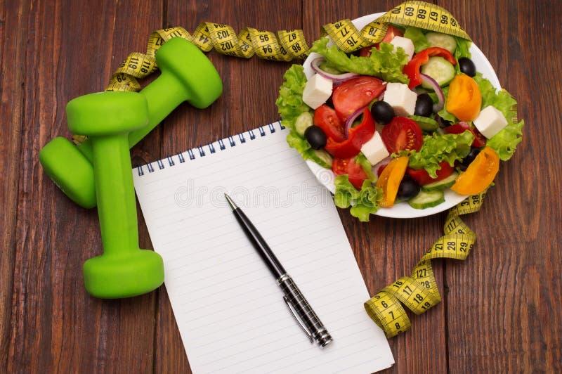 哑铃、菜沙拉和测量的磁带在土气木桌上 库存图片