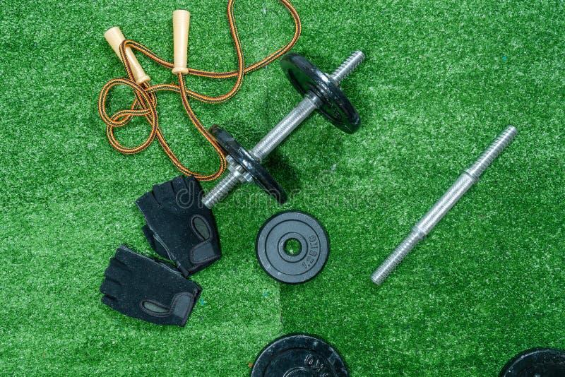 哑铃、重量圆盘、手套和辅助部件体育的,在草,健身 免版税库存图片