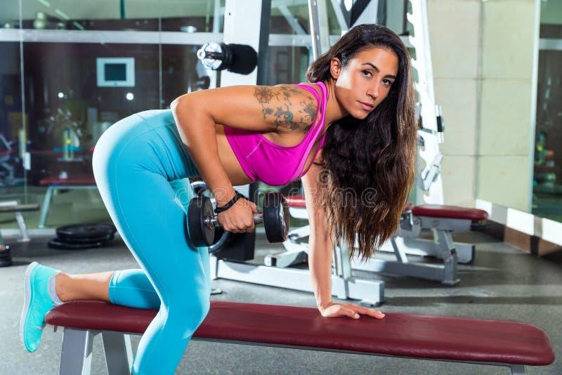 哑铃三头肌佣金在健身房的女孩锻炼 免版税库存图片