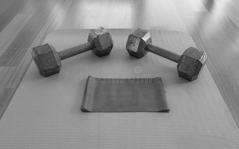 哑铃和锻炼带的黑白版本在瑜伽席子的一种家庭锻炼的 免版税库存图片