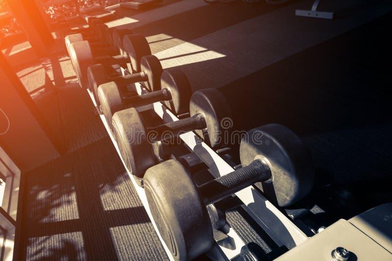 哑铃行在健身房的与hign对比和单色c 免版税图库摄影
