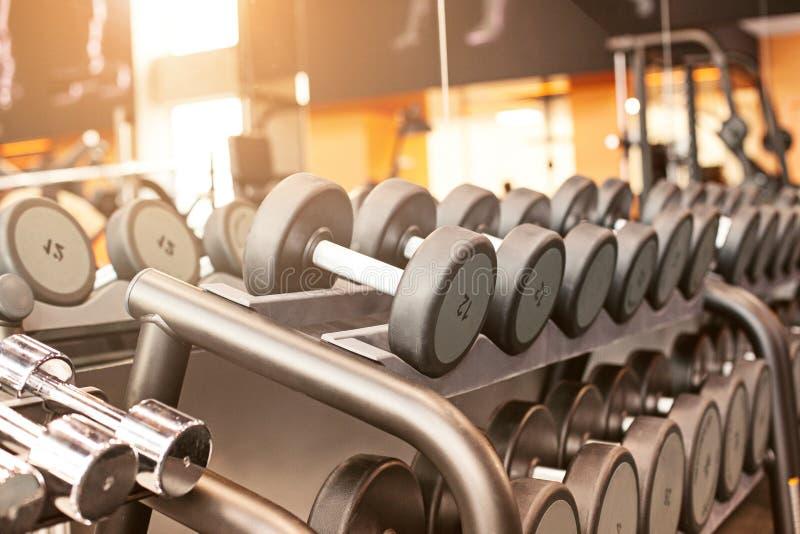 哑铃行在健身房的 免版税图库摄影