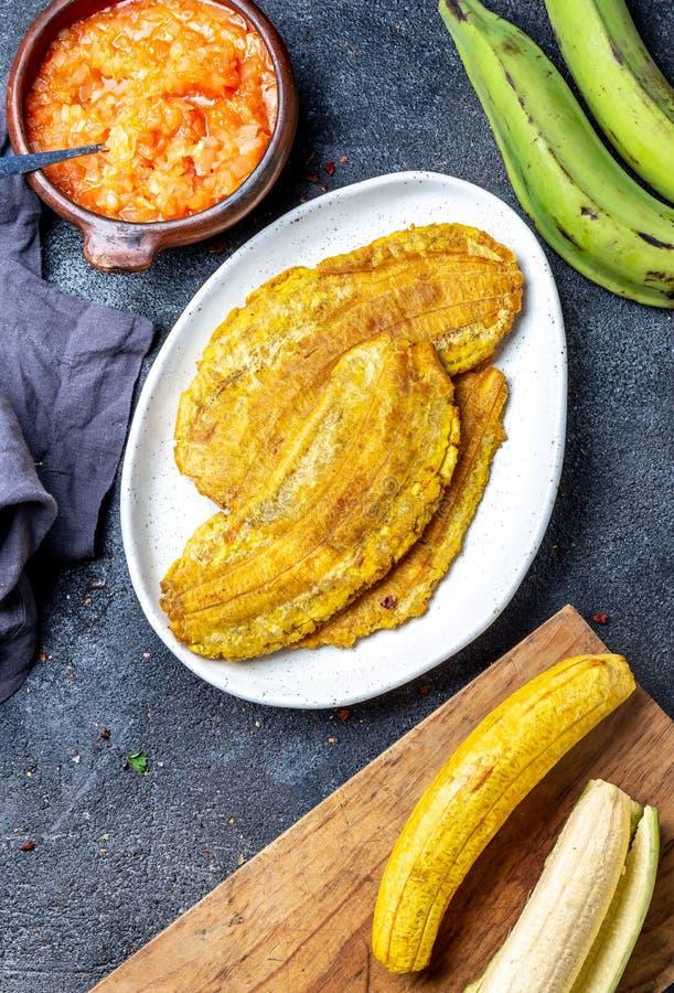 哥伦比亚的加勒比中美洲食物 Patacon或toston,油煎的和被铺平的整个绿色大蕉香蕉在白色 库存照片