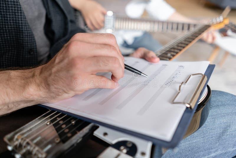 哥哥解释到他更加年轻一个如何使用关于音乐纸张的笔记在exapmple 免版税图库摄影