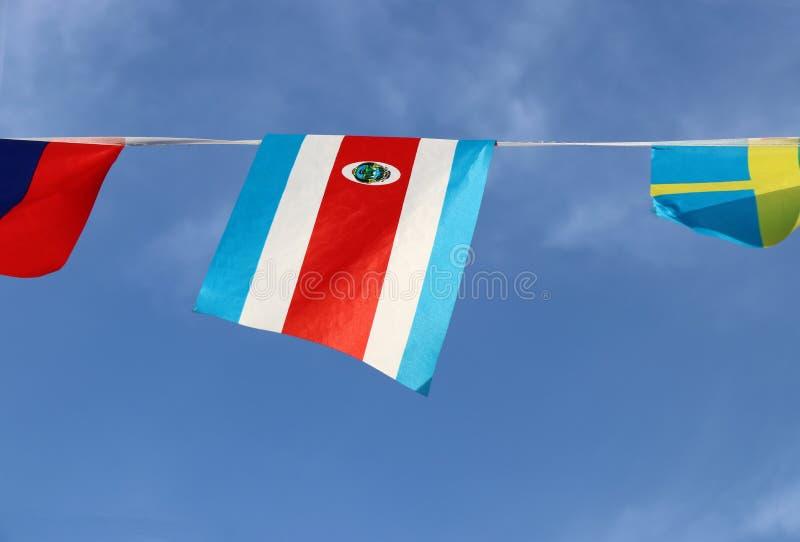 哥斯达黎加的微型织品路轨旗子三色红色蓝色的和白色与全国徽章,垂悬在绳索布料 免版税库存照片