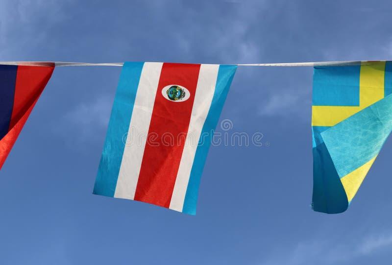 哥斯达黎加的微型织品路轨旗子三色红色蓝色的和白色与全国徽章,垂悬在绳索布料 免版税库存图片