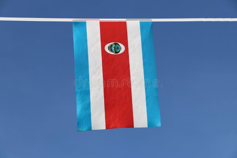 哥斯达黎加的微型织品路轨旗子三色红色蓝色的和白色与全国徽章,垂悬在绳索布料 库存图片