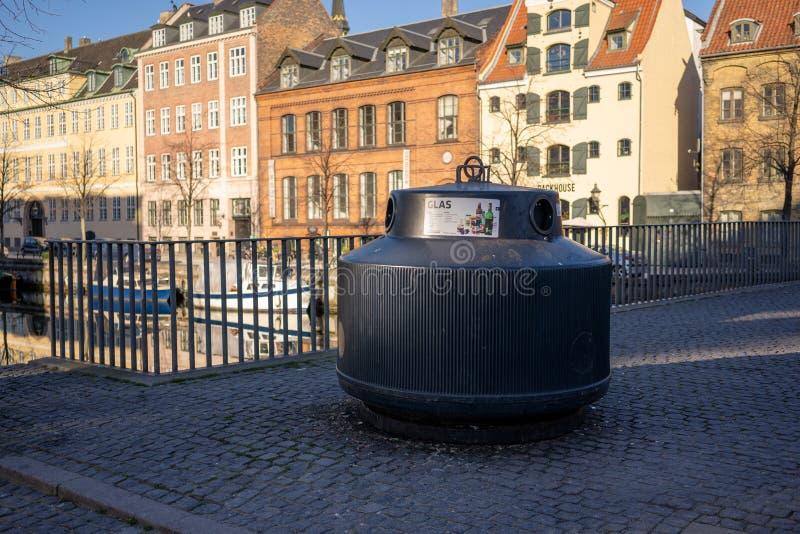 哥本哈根,丹麦- 2019年4月1日:玻璃的垃圾桶在一条运河旁边在Christianshavn在晴朗的天气的哥本哈根 免版税图库摄影