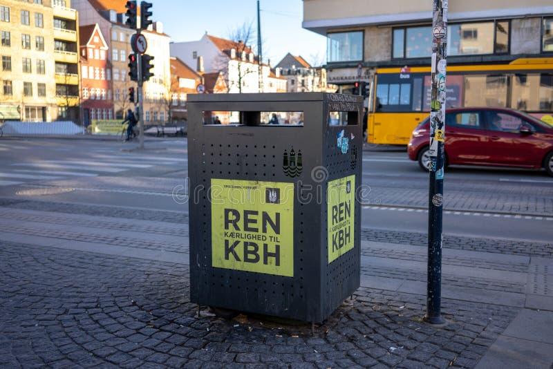 哥本哈根,丹麦- 2019年4月1日:在一条街道旁边的垃圾桶混杂的水的在Christianshavn,在晴朗的一条街道旁边 免版税库存照片