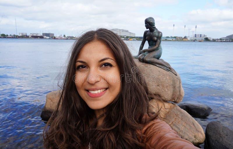 哥本哈根,丹麦- 2017年5月31日:拍与小的美人鱼的古铜色雕象的旅游女孩selfie照片 免版税库存图片