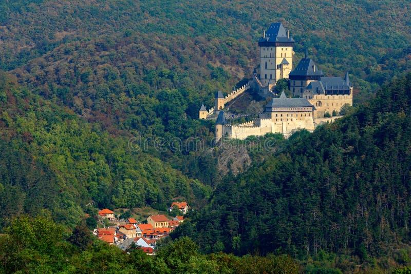 哥特式皇家城堡Karlstejn在秋天期间的绿色森林里,中波希米亚州,捷克共和国,欧洲 状态世袭的社会等级与村庄 库存照片