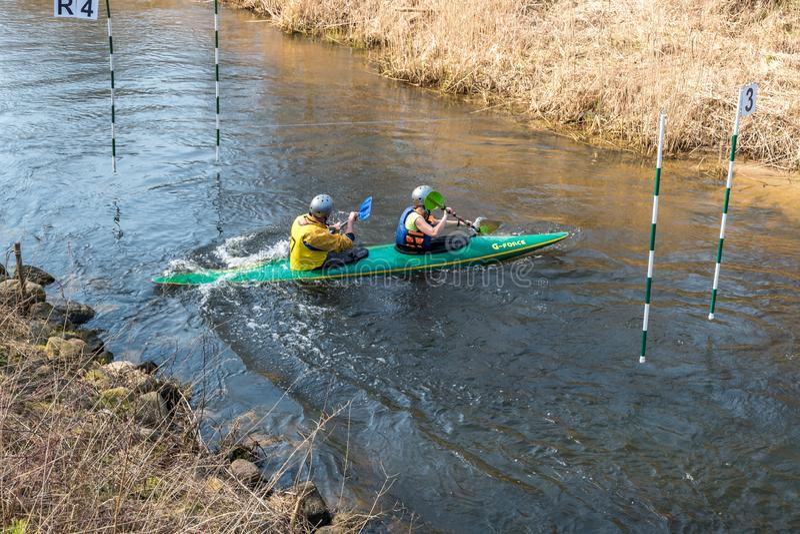 哥罗德诺,白俄罗斯- 2019年4月:皮船在吃力地荡桨快速的凉水的河的自由式竞争,胜利的精神 免版税库存图片