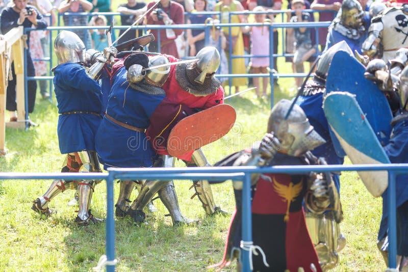 哥罗德诺,白俄罗斯- 2019年6月:小组中世纪马背射击的骑士战斗,在装甲、盔甲、锁子甲与轴和剑在名单上 免版税图库摄影