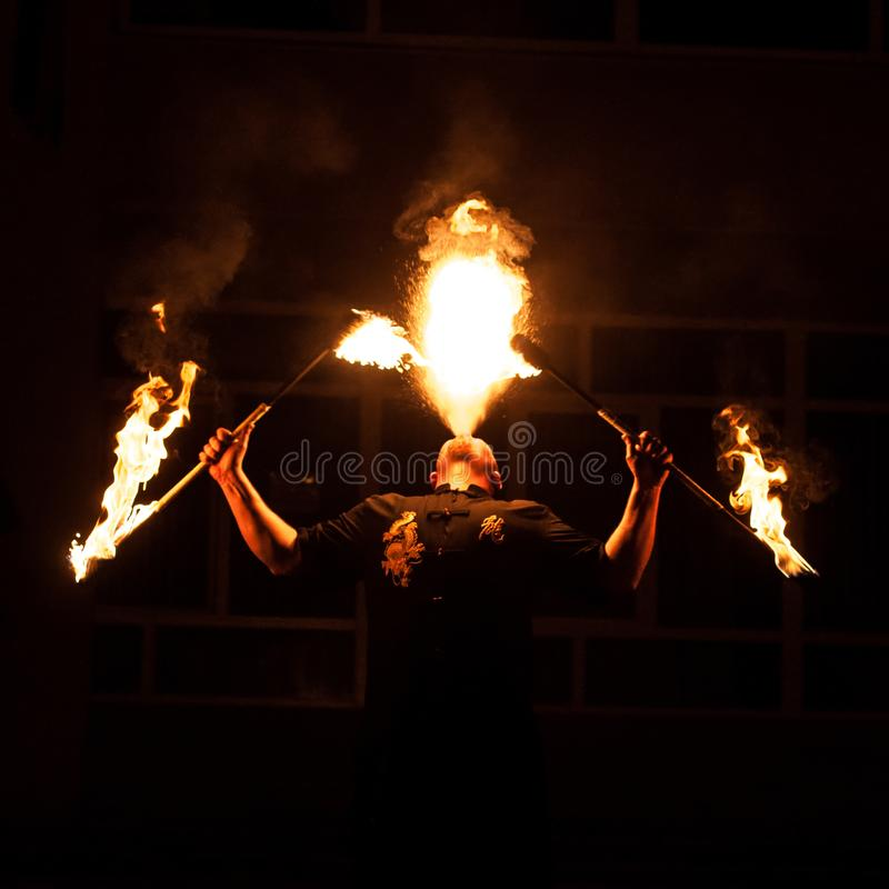 哥罗德诺,白俄罗斯- 2012火展示4月,30,火吹的表现,跳舞与火焰,有火工作的男性主要骗子在st 库存图片