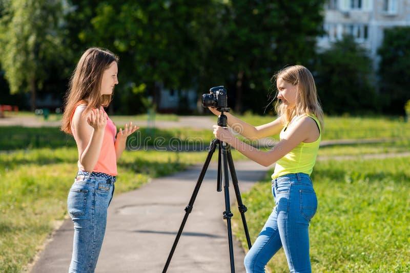 哪里小十几岁的女孩在夏天在公园记录在照相机的录影 情感地姿势示意与他的 免版税库存图片