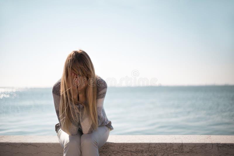 哭泣不快乐的妇女坐和 免版税库存图片