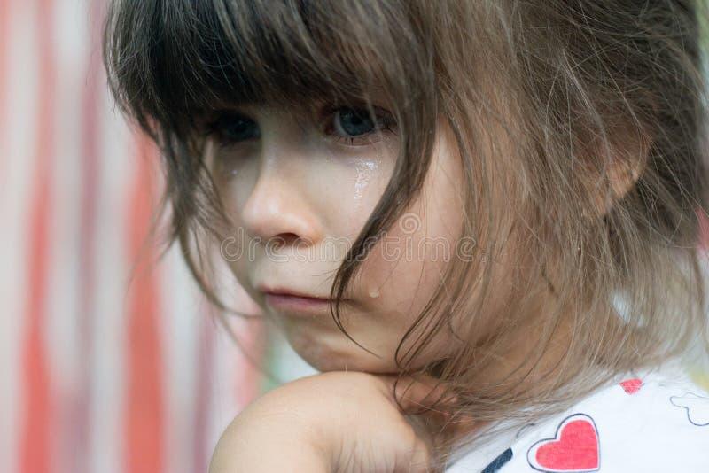 哭泣与泪花的小孩画象滚动下来她的面颊 库存照片