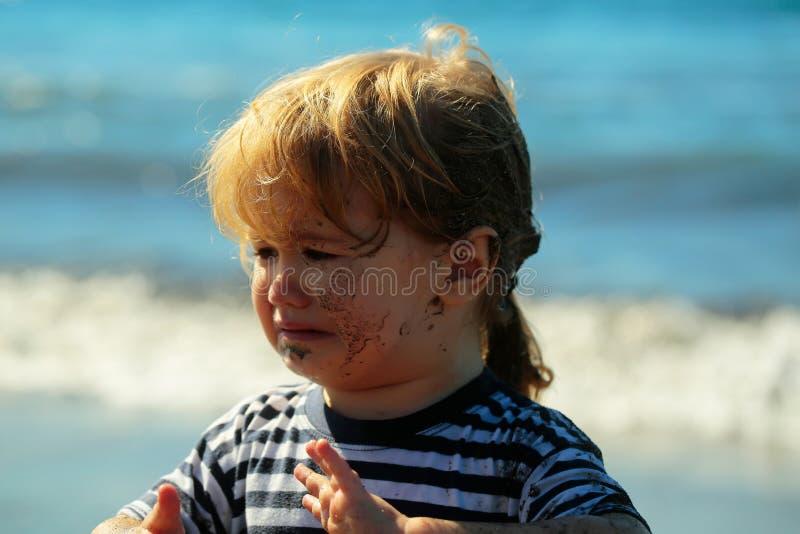 哭泣与肮脏的面孔和头发的逗人喜爱的不快乐的男婴 免版税库存照片