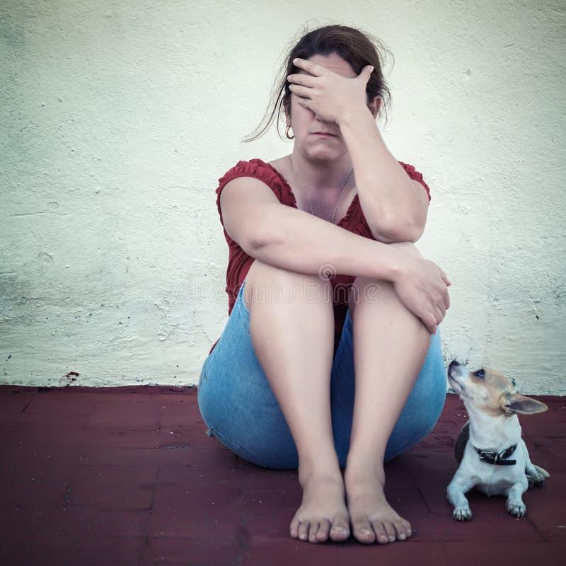 哭泣与除她以外的一条小狗的哀伤的妇女 免版税库存照片