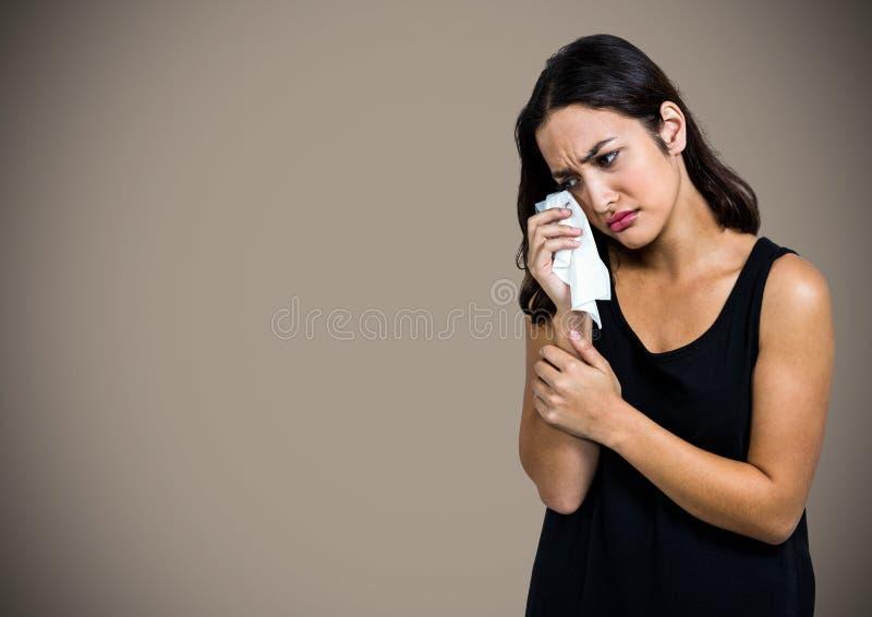 哭泣入组织的妇女反对棕色背景 图库摄影