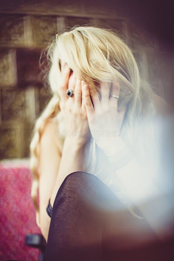 哭泣和掩藏她的面孔的坐的白肤金发的妇女 免版税库存照片