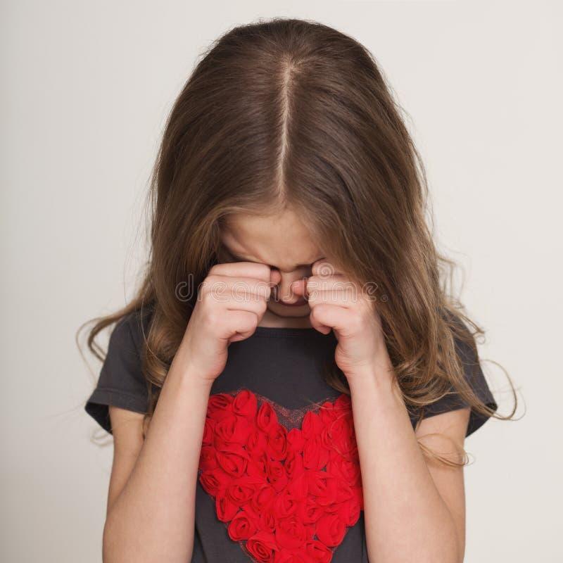 哭泣和摩擦她的眼睛的小女孩用她的手 图库摄影